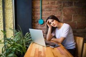 Woman holding computer, laptop tablet screen looking overwhelmed