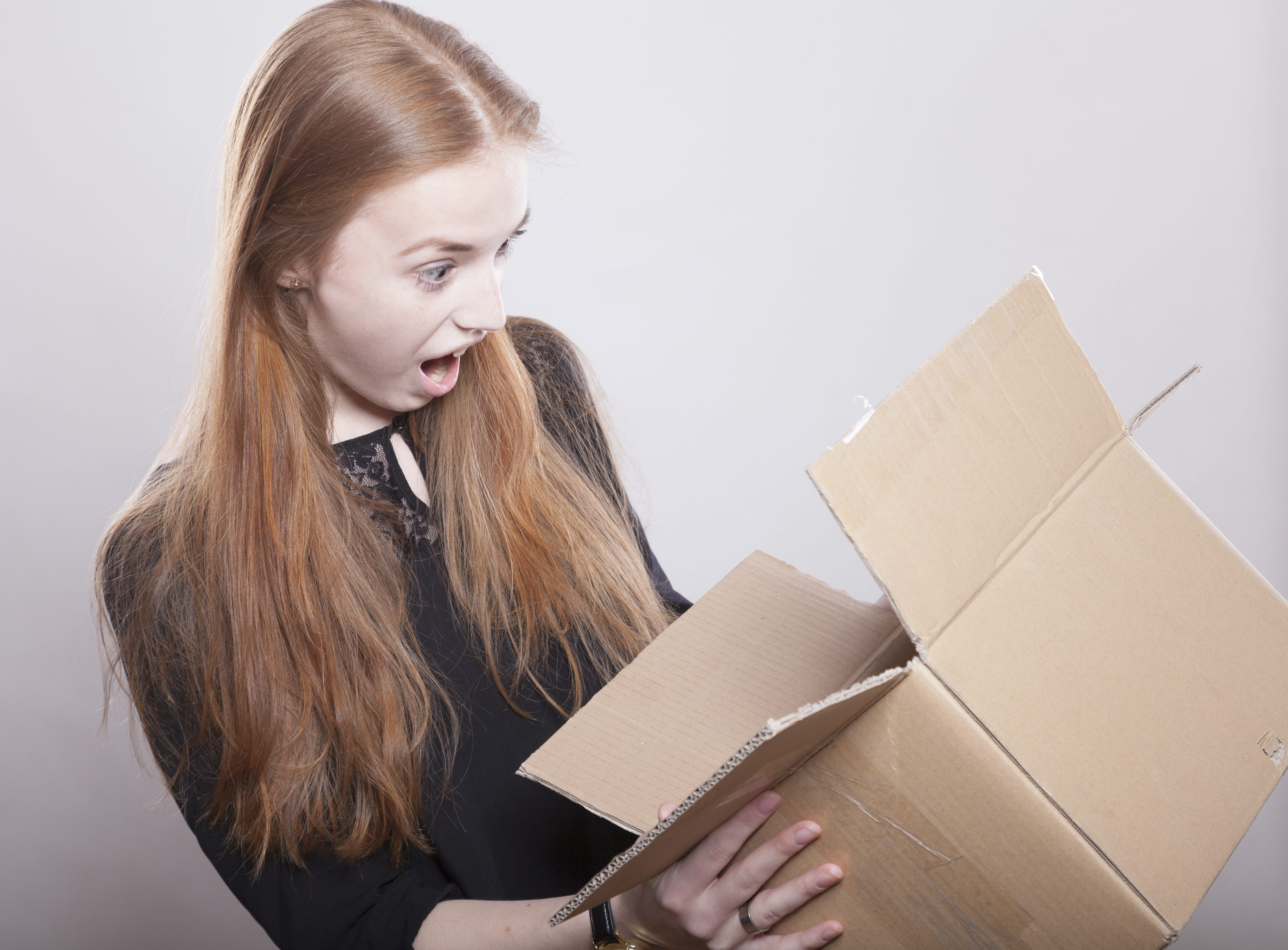surprised girl opening a box