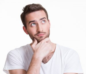 young thinking man looks up in casual cloths