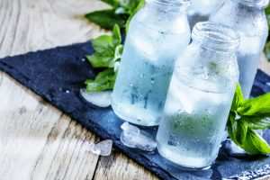 cold mineral water with ice in a misted glass bottles