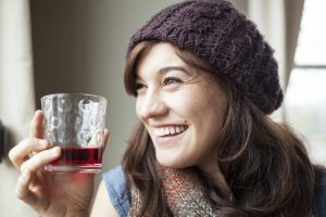 young woman drinking glass of cranberry juice